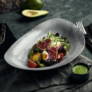 Nicoise salad with tuna on a gray plate, on a serving table. A beautiful dish from the chef, food photo, gray background, copy space, traditional French cuisine